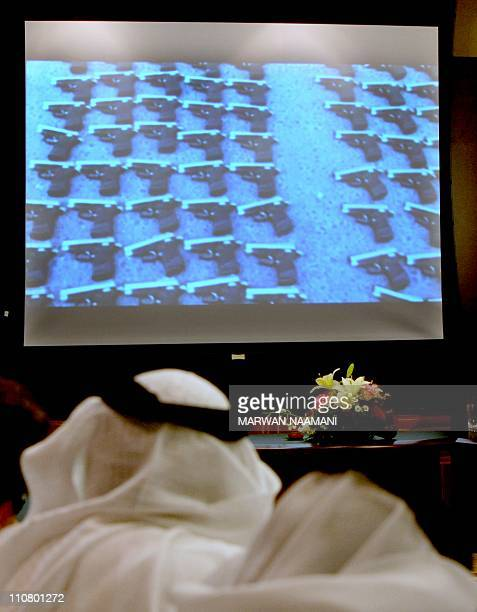 Journalists and police look at an image showing rows of pistols during a press conference by Dubai police chief Dahi Khalfan in Dubai on March 24...