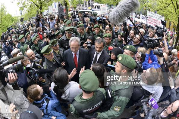 Journalists and policemen surround Munich's mayor Christian Ude as he listens to two young women of Turkish origin who try to get access to the...