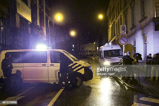 Journalists and residents stand near police vehicles as police set a large security perimeter in the city center of Verviers on January 15 during a...