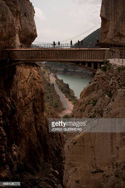 Journalists and visitors cross a bridge during a visit to the footpath 'El Caminito del Rey' a narrow walkway hanging and carved on the steep walls...
