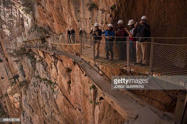 Journalists and visitors take photographs during a visit to the footpath 'El Caminito del Rey' a narrow walkway hanging and carved on the steep walls...