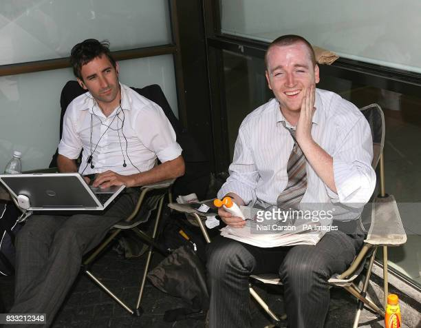 Journalists apply sun screen supplied by the National Lottery while waiting for Ireland's latest millionaire to arrive at the National Lottery...