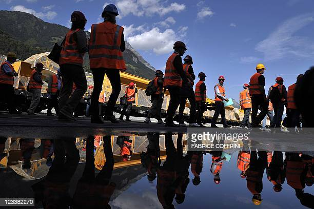 Journalists are reflected as they move to the entrance of one of the Gotthard base access tunnels during the launching of the installation of railway...