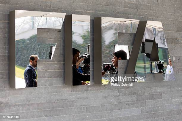 Journalists are reflected in the FIFA logo ahead of a press conference at the end of the FIFA Executive Comitee meeting at the FIFA headquarters on...