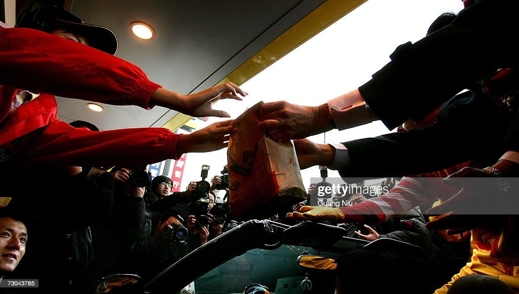 Journalists cover a McDonald's employee (L) handing food to customers at a new McDonald's drive-thru facility on January 19, 2007 in Beijing, China. McDonald's opened its first restaurant in mainland China in 1990, in Shenzhen, Guangdong province and now operates 760 restaurants countrywide, which employ over 50,000 people.
