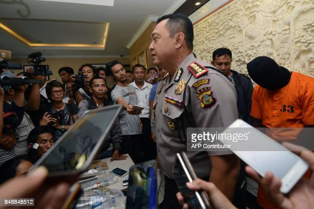 Journalists crowd a police official during a press conference as I Putu Astawa a suspect in the murder of an elderly Japanese couple in the...
