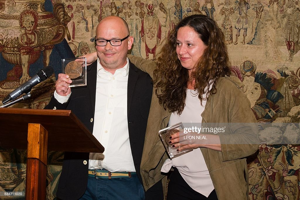 Journalists Etienne Huver (L) and Sophie Nivelle-Cardinale pose for pictures after being jointly awarded the Prix Albert Londres at the French Ambassador's residence in west London, on May 27, 2016. A series of reports from Africa and a film about the war in Syria were awarded the Prix Albert Londres for francophone journalists on Friday, as organisers drew attention to the need to protect whistle-blowers. / AFP / LEON