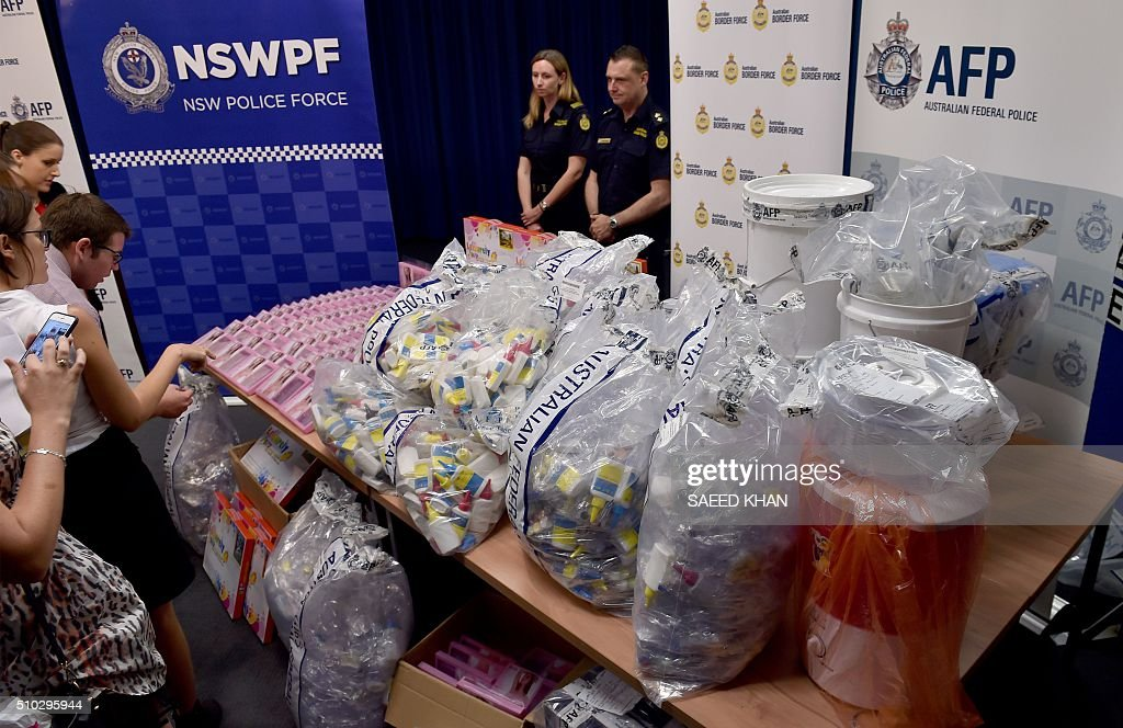 Journalists examine a haul of crystal methamphetamine concealed in packaging at the Australian Federal Police headquarters in Sydney on February 15, 2016. Australian police have seized more than 712 million USD in crystal methamphetamine, or ice, some concealed in gel bra inserts in one of the country's biggest drug busts. AFP PHOTO / Saeed KHAN / AFP / SAEED