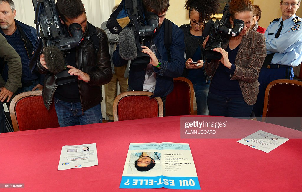 Journalists film a poster during a press conference of Blois' prosecutor on September 24, 2012 in Blois to announce that she reopens the case of an unidentified three or four-year-old girl found dead on August 11, 1987 on the motor highway A10, near Blois. AFP PHOTO ALAIN JOCARD