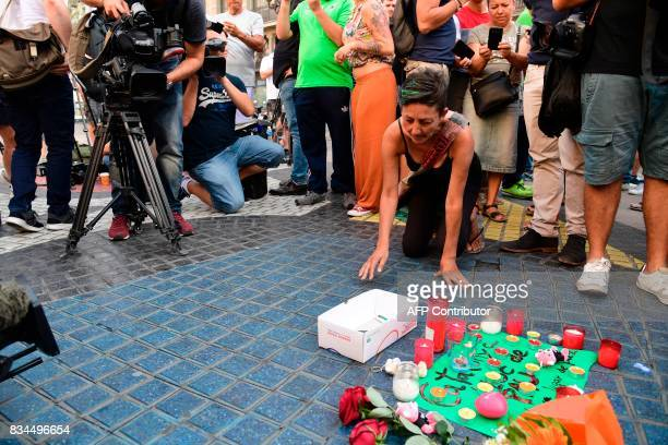 Journalists film a woman displaying a candle next to first flowers and a message to the victims on August 18 2017 on the spot where yesterday a van...