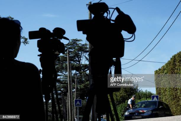 Journalists film French gendarmes standing next to their vehicles in front of the house of a man charged with kidnapping following the disapperance...