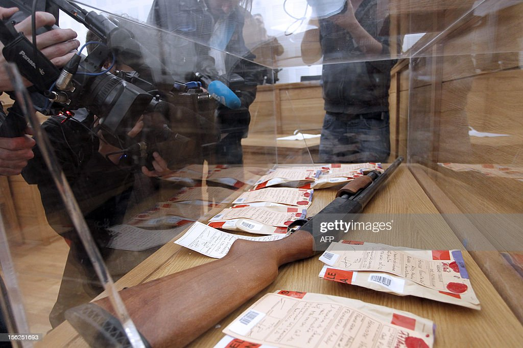 Journalists film seals, including a rifle, in a courtroom on November 12, 2012 in Ajaccio prior to the start of the trial of 19-year-old boy for shooting dead his parents and 10-year-old twin brothers in 2009. The accused, named as Andy, exterminated the entire family in August 2009 with his father's Winchester rifle in an act he said occurred in a trance-like state.