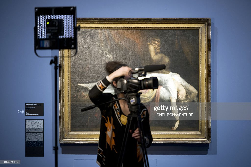 A journalists films in front of the 'Le Cauchemar' (The Nightmare) painting by Johann Heinrich Fussli, displayed during the exhibition 'The Angel of the Odd. Dark Romanticism from Goya to Max Ernst' at the Orsay museum in Paris, on March 4, 2013. The exhibition will run from March 5 until June 9, 2013. AFP PHOTO / LIONEL BONAVENTURE CAPTION