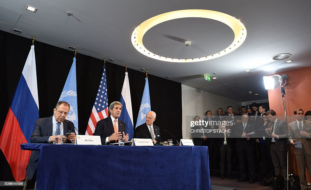 Journalist's follow a news conference of Russian Foreign Minister Sergei Lavrov, US Secretary of States John Kerry and UN Special Envoy for Syria Staffan de Mistura (L-R) after the International Syria Support Group (ISSG) meeting in Munich, southern Germany, on February 12, 2016. / AFP / Christof STACHE