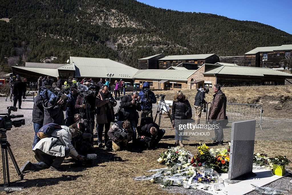 Journalists gather around a stele carved in French German Spanish and English in memory of the victims of the Germanwings Airbus A320 crash in the...