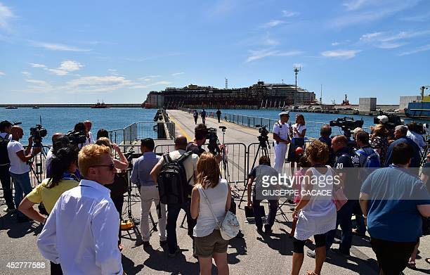 Journalists gather at the Italian port of Genoa as the refloated wreck of the Costa Concordia cruise liner is towed on July 27 2014 The wreck of the...