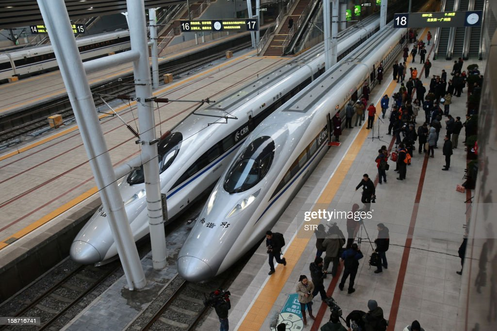 Journalists gathers beside the high speed train of the new 2,298-kilometre (1,425-mile) line between Beijing and Guangzhou as it waits to start off in Beijing on December 26, 2012. China started service on December 26 on the world's longest high-speed rail route, the latest milestone in the country's rapid and -- sometimes troubled -- super fast rail network. The opening of this new line means passengers will be whisked from the capital to the southern commercial hub in just eight hours, compared with the 22 hours previously required. CHINA