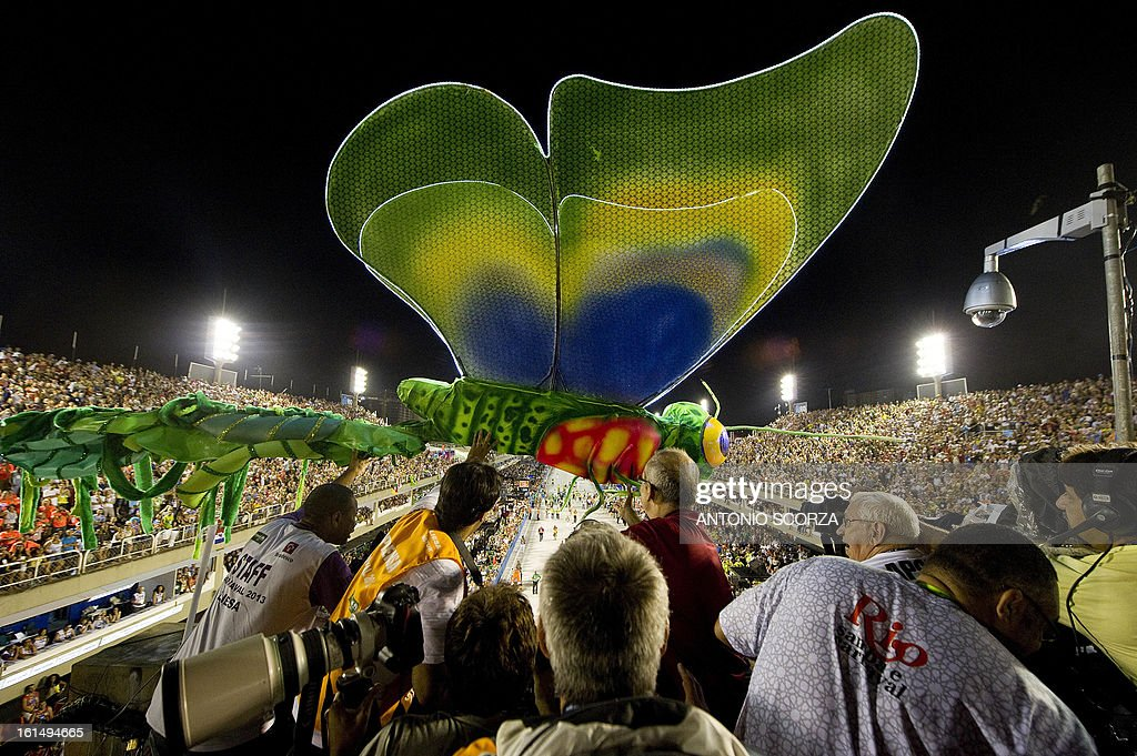 Journalists grab a dragonfly statue, part of Mangueira samba school float, that crashed against a television tower, during their performance on the second night of Carnival parade at the Sambadrome in Rio de Janeiro, Brazil on February 11, 2013.