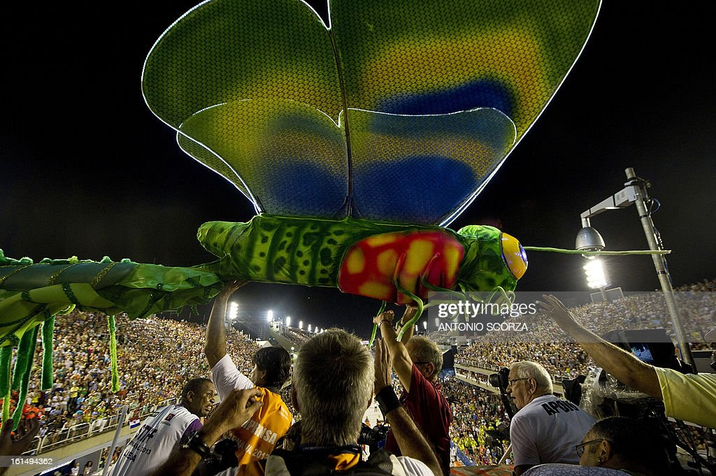 Journalists help to pass a dragonfly statue, part of Mangueira samba school float, that crashed against a television tower, during their performance on the second night of Carnival parade at the Sambadrome in Rio de Janeiro, Brazil on February 11, 2013.
