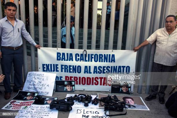 Journalists hold a banner during a demonstration against violence targeting reporters outside the Attorney General of the Republic building on March...
