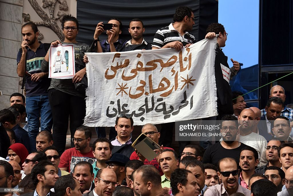 Journalists hold a banner reading in Arabic: 'I am a journalist not a terrorist' during a demonstration outside the Journalist Syndicate headquarters in Cairo calling for the sacking of the interior minister following an unprecedented police raid to arrest two reporters on May 4, 2016. / AFP / MOHAMED