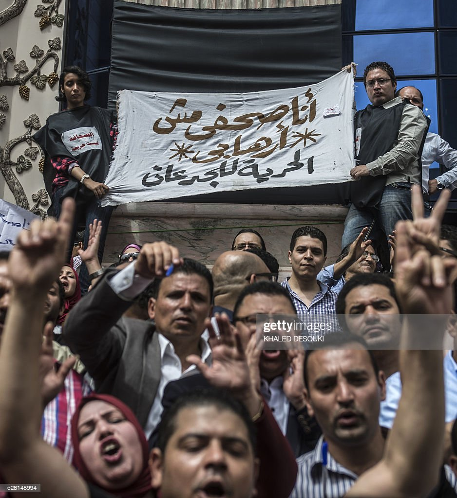 Journalists hold a banner reading in Arabic: 'I am a journalist not a terrorist' during a demonstration outside the Journalist Syndicate headquarters in Cairo calling for the sacking of the interior minister following an unprecedented police raid to arrest two reporters on May 4, 2016. / AFP / KHALED