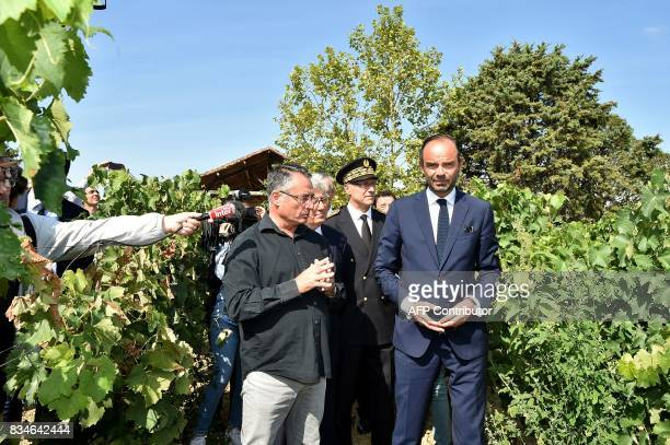 A journalists hold out a microphone as French Prime Minister Edouard Philippe listens to wine and armagnacs producer Michel Baylac as they stand in a...