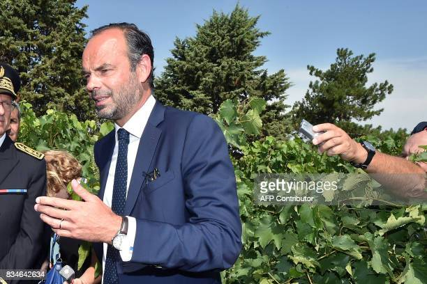 A journalists hold out a microphone as French Prime Minister Edouard Philippe speaks to the wine and armagnacs producer as they stand in a vineyard...