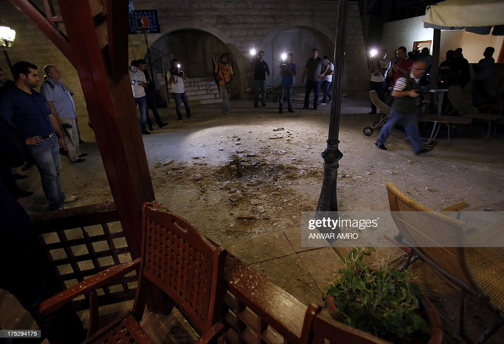 Journalists inspect the damage at a private residence where one of two rockets fired from an unknown location exploded in the early hours of August 2, 2013, just metres from an entrance to the presidential palace in Baabda, around eight kilometres southeast of the Lebanese capital Beirut. The official news agency ANI said the second rocket fell near a Lebanese army training camp in the region of Baabda, causing no casualties as tensions mounted in the east Mediterranean country over the conflict in neighbouring Syria.