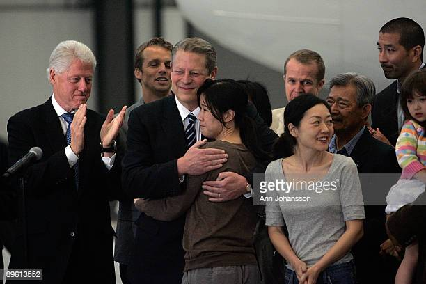 Journalists Laura Ling hugs former Vice President Al Gore as they stand with Euna Lee and former President Bill Clinton at Hangar 25 on August 5 2009...