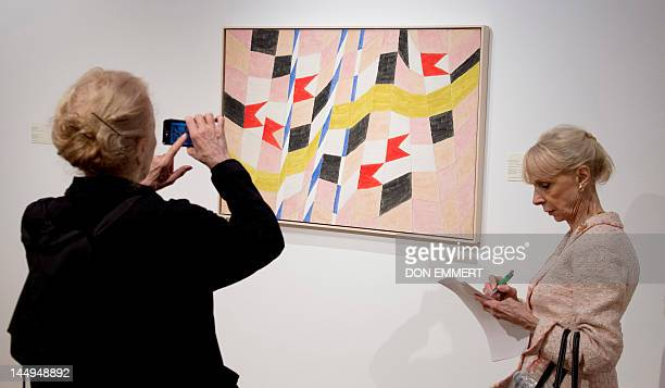 Journalists look at Brazilian artist Alfredo Volpi's painting 'Bandeirinhas com mastros e fita' on May 21 2012 at Christie's in New York Christie's...