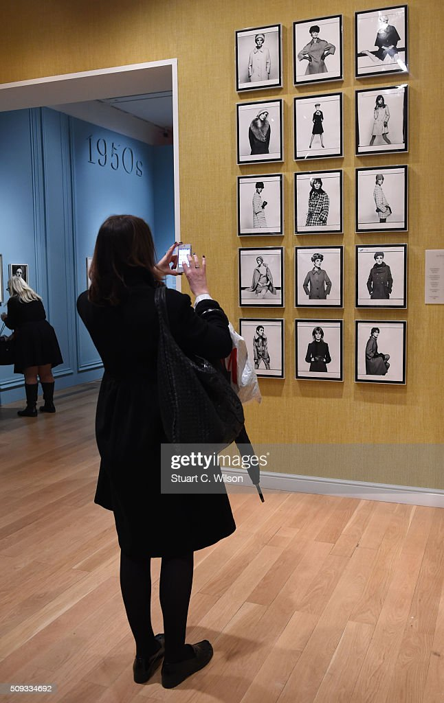 A journalists looks at images on the wall at the press preview for 'Vogue 100: A Century of Style' exhibiting the photographs that has been commissioned by British Vogue since it was founded in 1916 at National Portrait Gallery on February 10, 2016 in London, England.