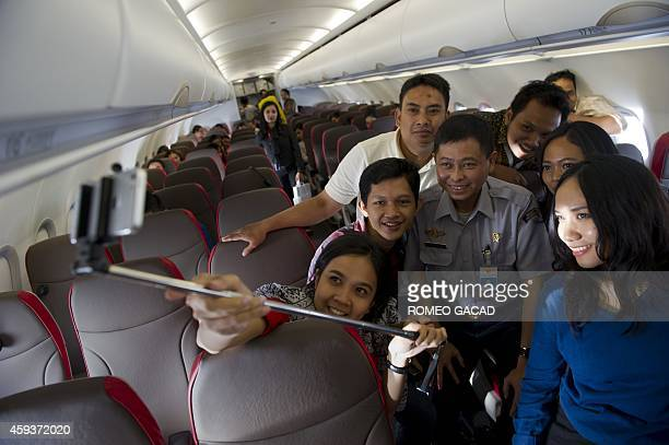 Journalists make a selfie with Indonesian Transport Minister Ignasius Jonan aboard the inaugural flight of a new Airbus A320 of Indonesia's premier...