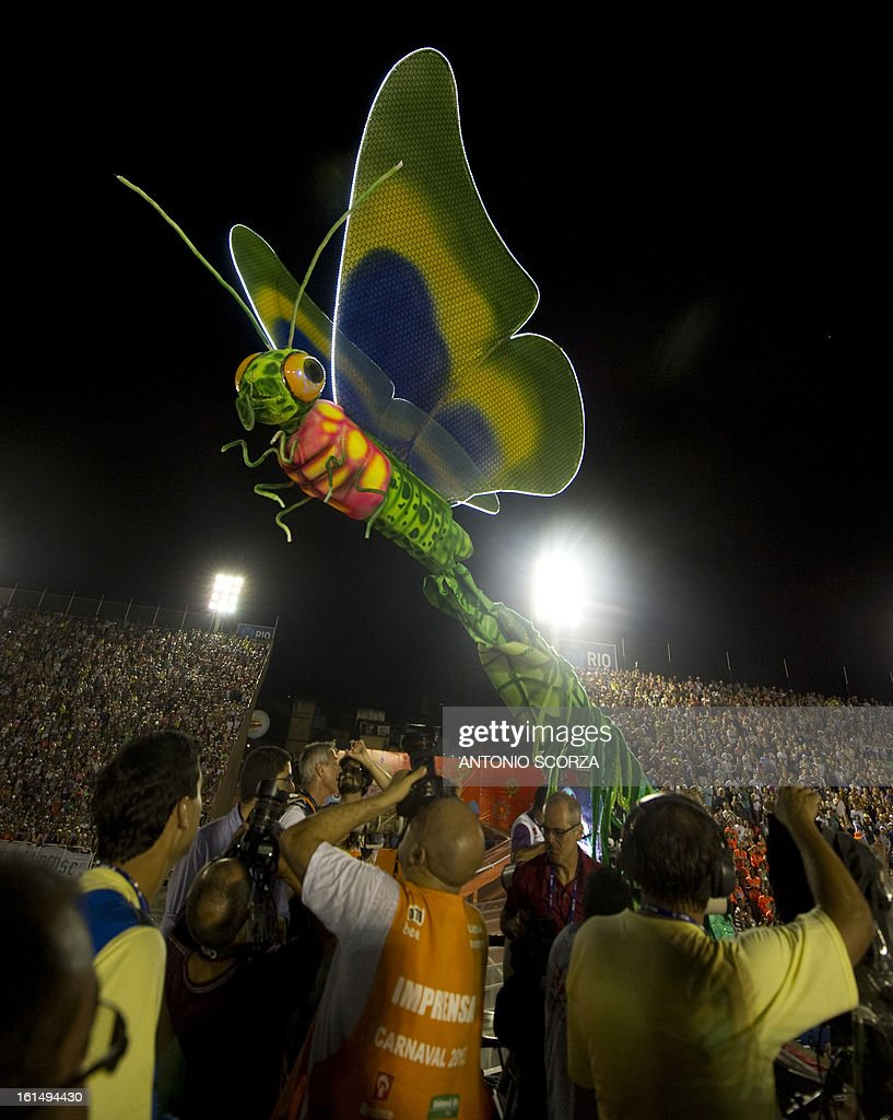 Journalists observe as a dragonfly statue, part of Mangueira samba school float, crashes against a television tower, during their performance on the second night of Carnival parade at the Sambadrome in Rio de Janeiro, Brazil on February 11, 2013.