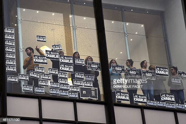 Journalists of international press agency Agence FrancePresse hold signs reading 'Je suis Charlie' at their headquarters in Paris as they observe a...