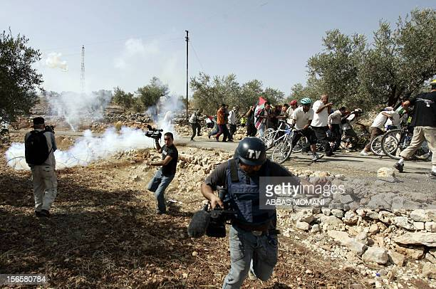 Journalists Palestinian foreign and Israeli peace activists run for cover as the Israeli army fires stun grenades during a rally highlighting the...