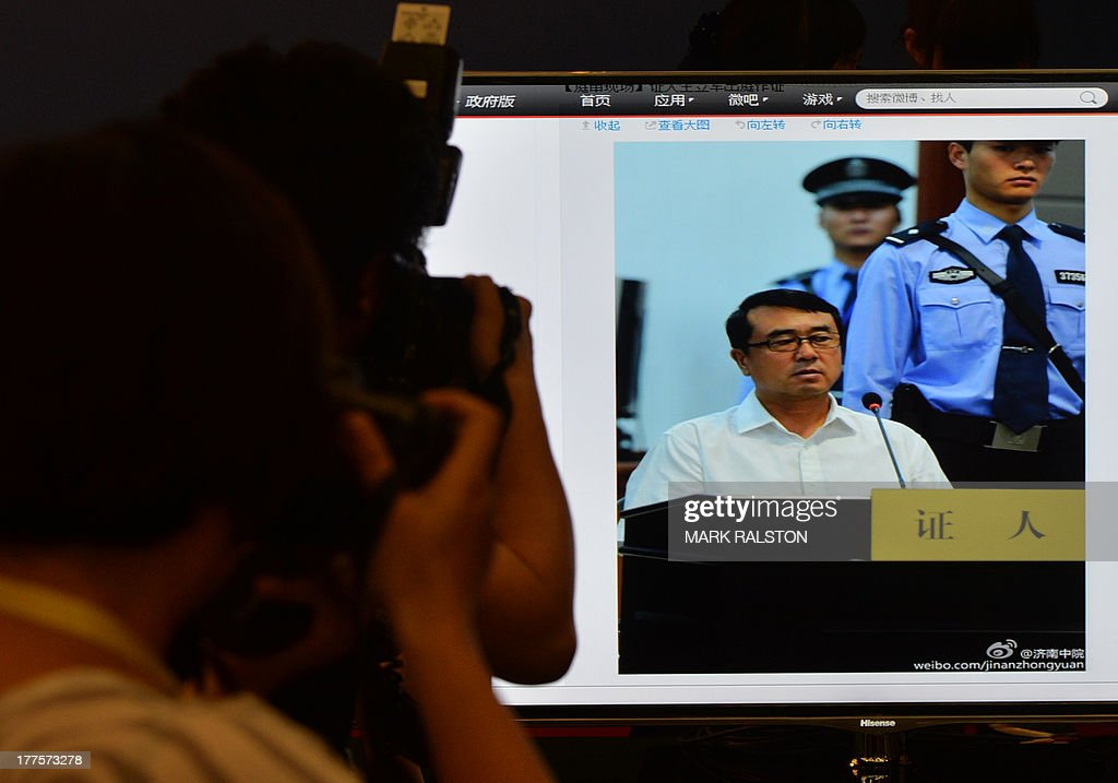 Journalists photograph a television showing images of former police chief Wang Lijun as he gives evidence on the third day of the trial of disgraced politician Bo Xilai at the Intermediate People's Court in Jinan, Shandong Province on August 24, 2013. Once one of China's highest-flying politicians, Bo Xilai found himself in the criminal dock on trial for bribery and abuse of power in the country's highest-profile prosecution in decades. AFP PHOTO/Mark RALSTON