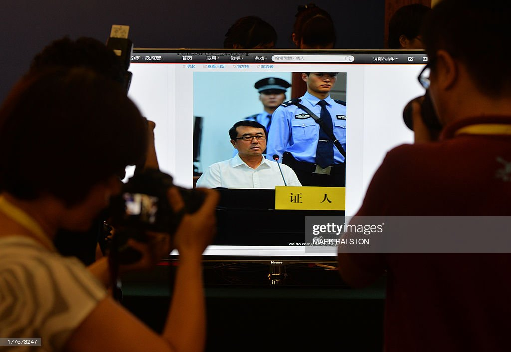 Journalists photograph video of former police chief Wang Lijun as he gives evidence on the third day of the trial of disgraced politician Bo Xilai at the Intermediate People's Court in Jinan, Shandong Province on August 24, 2013. Once one of China's highest-flying politicians, Bo Xilai found himself in the criminal dock on trial for bribery and abuse of power in the country's highest-profile prosecution in decades. AFP PHOTO/Mark RALSTON