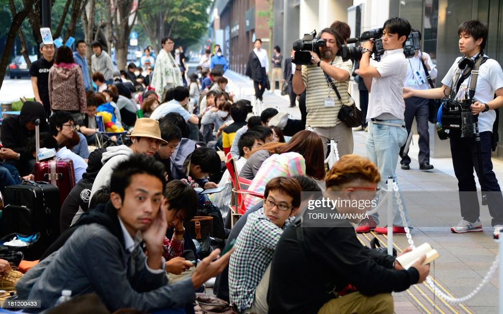 Journalists (R) record footage of customers queueing before being let into an outlet of Japan's biggest mobile carrier, NTT Docomo, to purchase new iPhones in Tokyo on September 20, 2013. Apple's new iPhone 5s and 'cheap' 5C models on September 20 went on sale in Japan. AFP PHOTO/Toru YAMANAKA