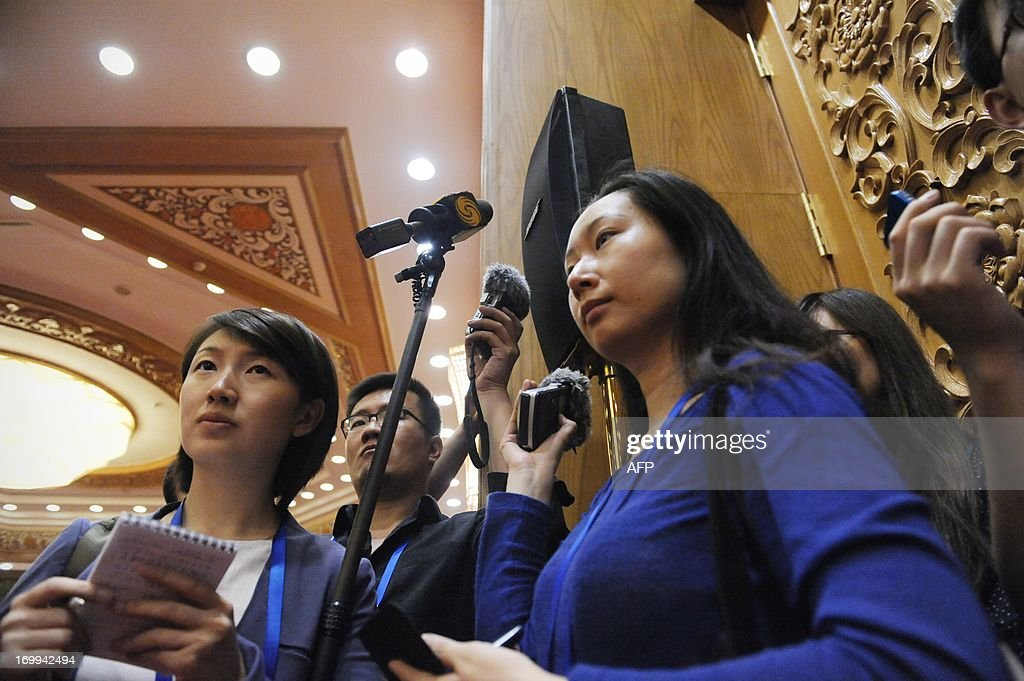Journalists record from a loudspeaker as China's Premier Li Keqiang (not pictured) meets with CEOs who will attend the Chengdu Fortune Forum at the Great Hall of the People in Beijing on June 5, 2013. The Fortune Global Forum will be held from 6-8 June in Chengdu, southwest China's Sichuan province.