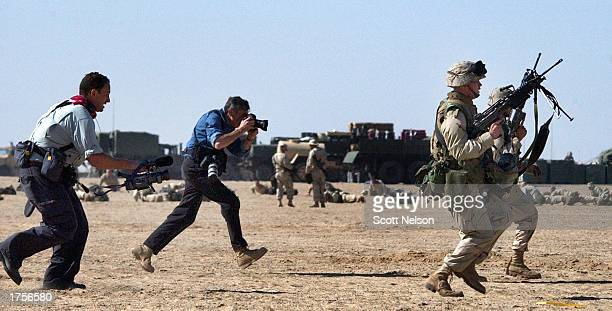 Journalists scramble behind US Marines from 3rd Battallion 1st Marine Division as they practice squad rushes February 1 2003 at Living Support Area...