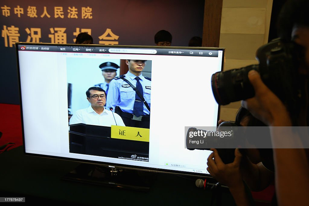 Journalists shoot a screen showing a picture of former police chief Wang Lijun as he gives evidence on the third day of the trial of disgraced politician Bo Xilai at the Jinan Intermediate People's Court on August 24, 2013 in Jinan, China. Ousted Chinese politician Bo Xilai is standing trial on charges of bribery, corruption and abuse of power for a third day. Bo Xilai made global headlines last year when his wife Gu Kailai was charged and convicted of murdering British businessman Neil Heywood.