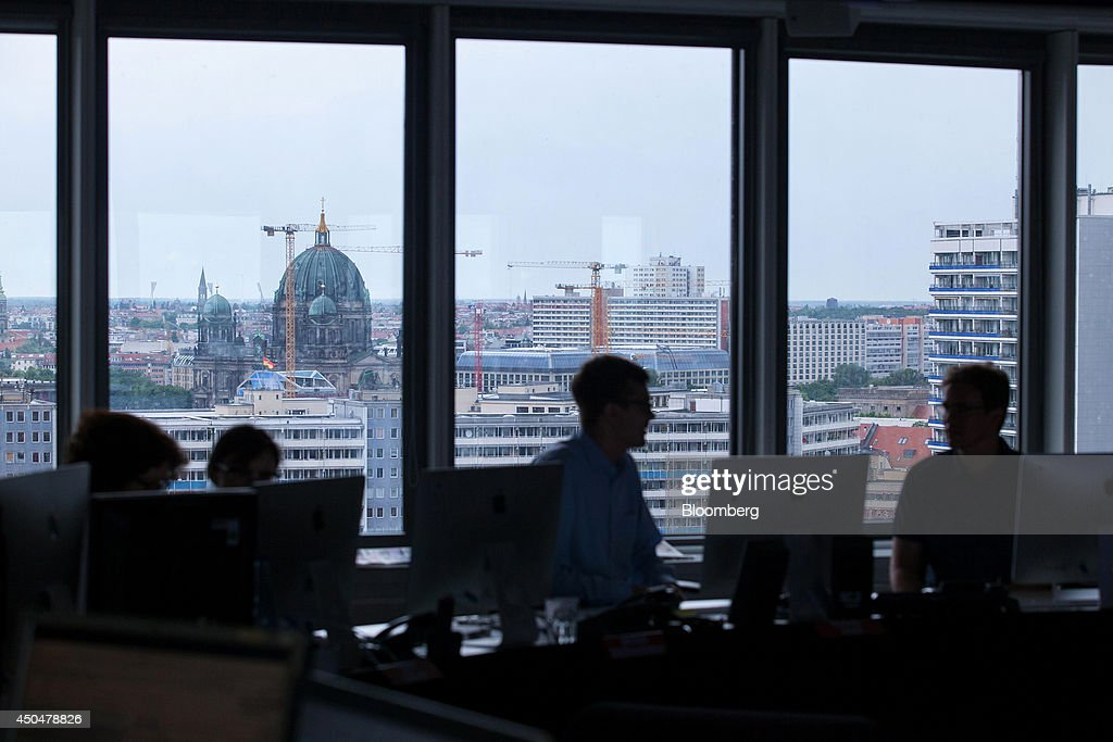 Journalists sit at desktop computers in the newsroom of tabloid newspaper Bild, published by Axel Springer SE, as construction cranes are seen beyond on the city skyline, in Berlin, Germany, on Wednesday, June 11, 2014. Axel Springer, Europe's biggest newspaper publisher, is working with JPMorgan Chase & Co. and Citigroup Inc. on an initial public offering of its digital-classifieds business, people familiar with the matter said. Photographer: Krisztian Bocsi/Bloomberg via Getty Images