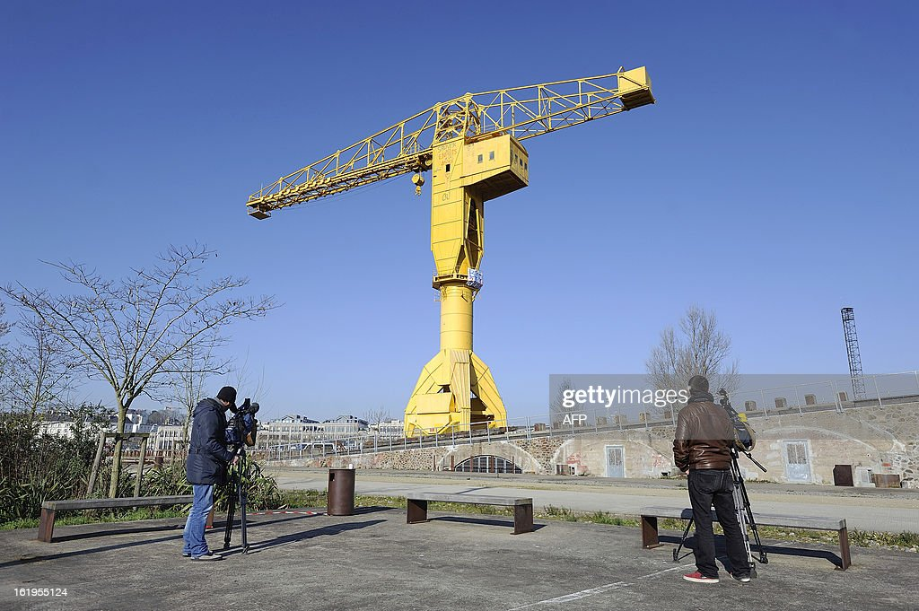 Journalists stand in front of a 43-meter crane where Serge Charnay, a father denied access to his son, was perched on February 18, 2013 in the western French city of Nantes for a fourth day of a protest for his rights as a father. Charnay has struggled to win back the right to see his son, born in 2006, after losing custody and all visiting rights when he was accused of kidnapping the boy. AFP PHOTO JEAN-SEBASTIEN EVRARD