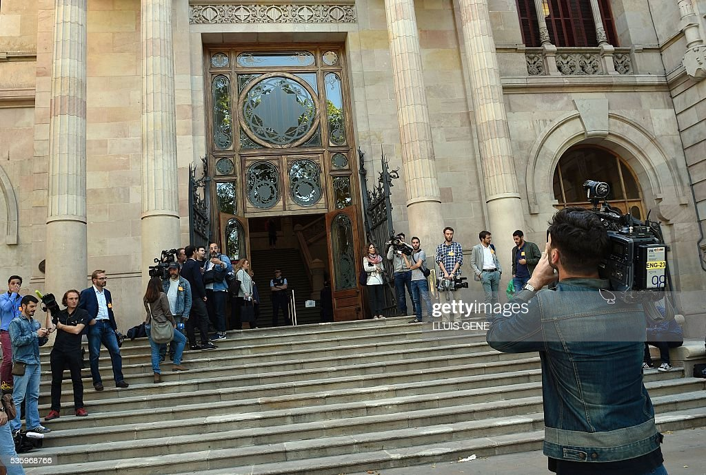 journalists stand in front of the courhouse in Barcelona on May 31, 2016 where Messi is to face judges in a tax fraud case. Messi and his father, Jorge Horacio Messi, are accused of using a chain of fake companies in Belize and Uruguay to avoid paying taxes on 4.16 million euros ($4.7 million) of Messi's income earned through the sale of his image rights from 2007-09. GENE