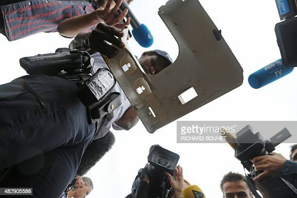 Journalists stand next to a police officers holding a piece of plastic found on the sea front of SaintDenis on the French Indian Ocean island of La...