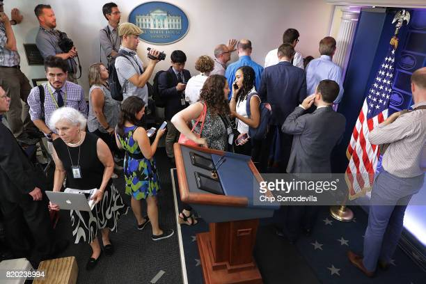 Journalists stand outside the entrance to the White House press office after it was learned that Press Secretary Sean Spicer has resigned July 21...