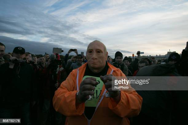 Journalists surround a protester wearing a rubber mask depicting Russian President Vladimir Putin during an unauthorized rally called by opposition...