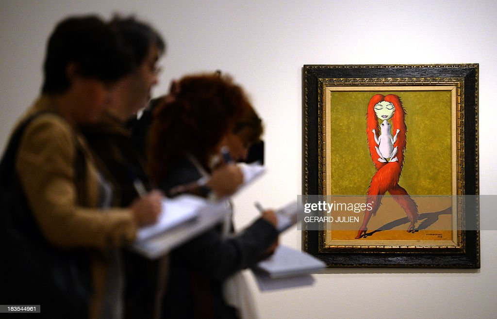Journalists take notes past the painting 'Objet qui rêve II'' by Victor Brauner during the exhibition entitled 'Surrealism and the Dream' at the Thyssen-Bornemisza museum in Madrid, on October 7, 2013. AFP PHOTO/ GERARD JULIEN