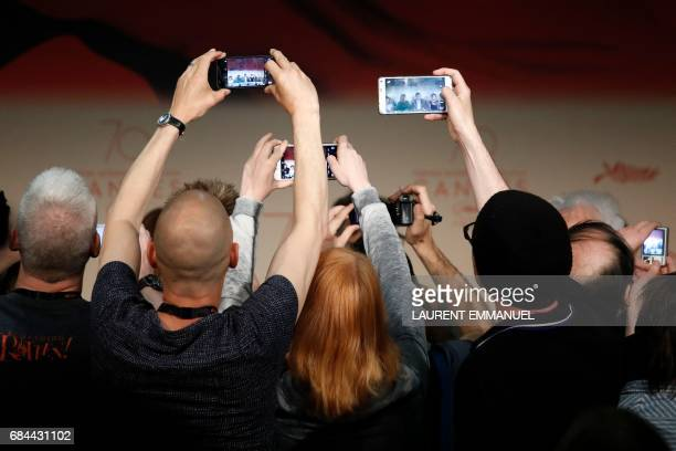 TOPSHOT Journalists take photos of US actress Julianne Moore and US director Todd Haynes arriving to attend on May 18 2017 a press conference for the...